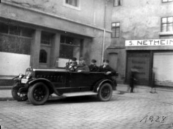 Paul Netheim in 1928 at the wheel of his car, nearest the camera; in the background is Rosenstrasse with a side view of the business